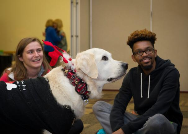 Dogs On Call therapy dog Wrigley, a golden retriever, wears a reindeer collar and is making two V C U students smile
