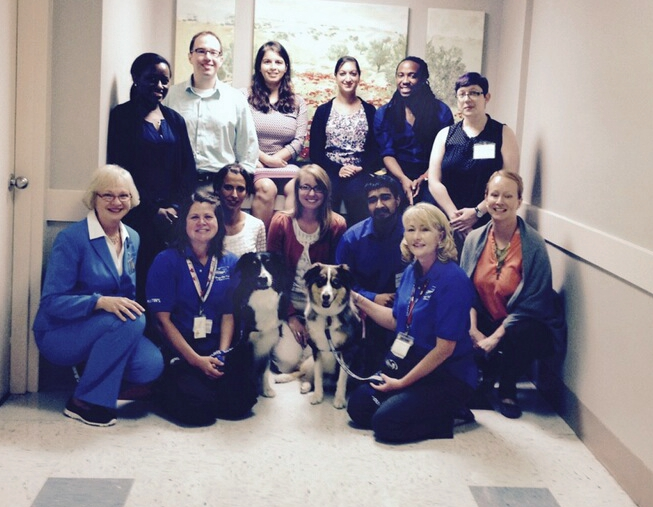Two Dogs On Call therapy dogs, Houdi and Moose who are both Australian Shepherds, pose alongside their handlers, Dr. Sandra Barker and several students.