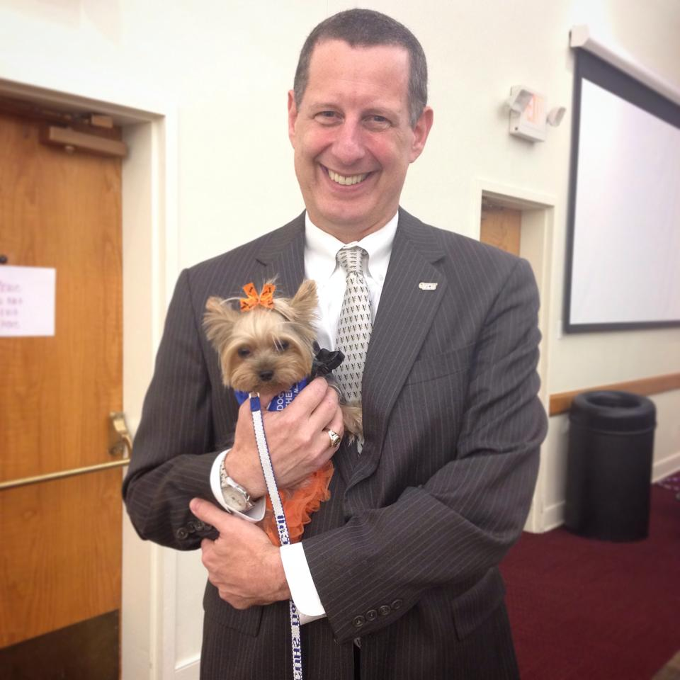 Dr. Reuban Rodriguez of V C U is wearing a gray suit and smiling while holding Dogs On Call therapy dog Winnie, a yorkie.